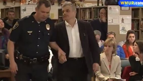 William Baer is lead out of a school board meeting by an armed officer who cuffs him in the hallway